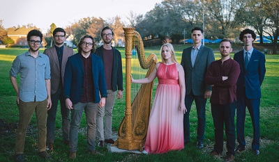 Anna Jalkeus and her ensemble standing in a grassy park-like setting