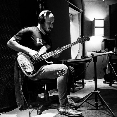 Matt Wigton playing electric bass in a recording studio