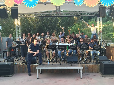 Rich DeRosa and the student big band he coached on an outdoor stage in Rome with trees behind it